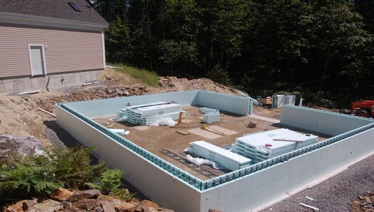 Several insulated form units and the exterior perimeter drains have been installed. The compacted floor serves as the staging area. Note that all the components of the walls are neatly organized for an efficient building process.